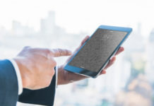 Businessman Holding iPad in front of a skyline