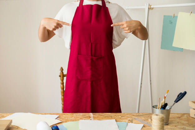 A Girl Pointing At Her Red Colored Apron PSD Mockup