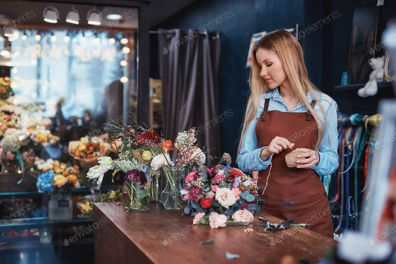 A Young Girl In An Apron In a Flower Shop