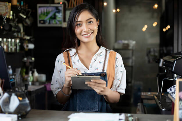 Asian Women Wearing Apron Smiling In A Coffee Shop Mockup