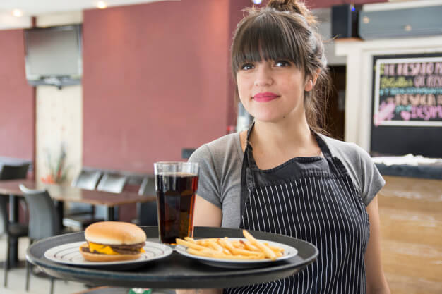 Female Waitress Holding Food In An Apron