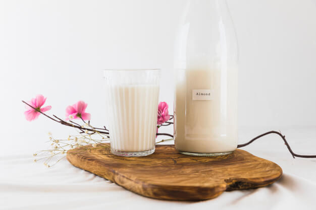 Glass And Bottle Filled With Milk Placed With Some Flowers