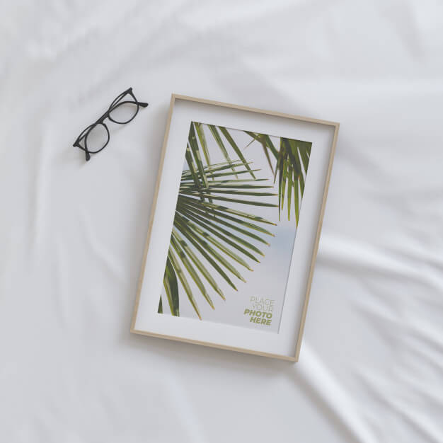 Photo frame mockup with glasses on bed Premium Psd