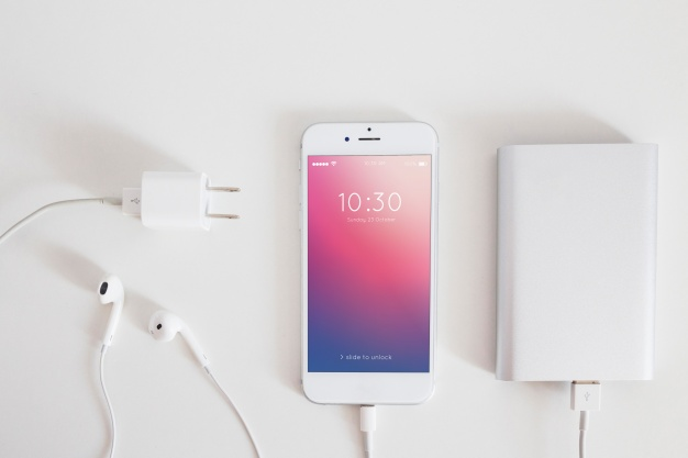 Smartphone mockup with charging cable and earphones Free Psd
