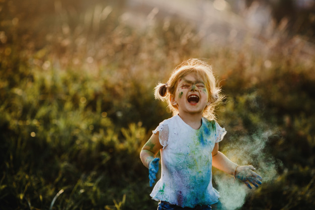 A Charming Little Girl In White T-shirt Playing With Colors.