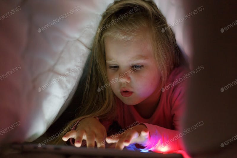 A Little Girl Playing On Her Tablet Under TheBlanket PSD Template.