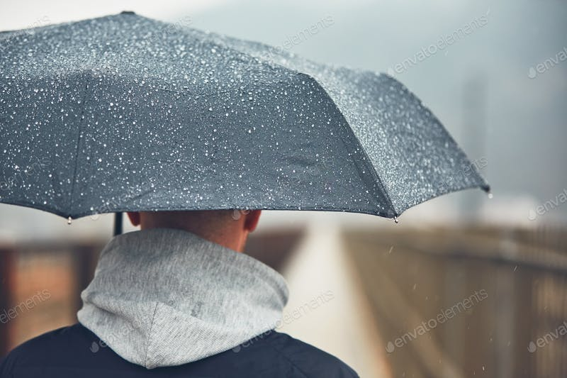 A Man Holding An Umbrella In Rain PSD Template.