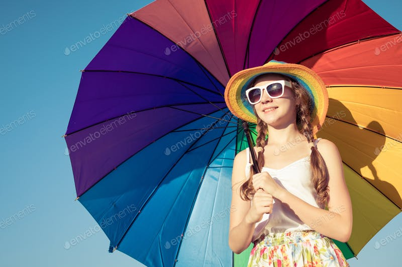 A Teen Girl  Standing On a beach Holding A Colorful Umbrella PSD Template.