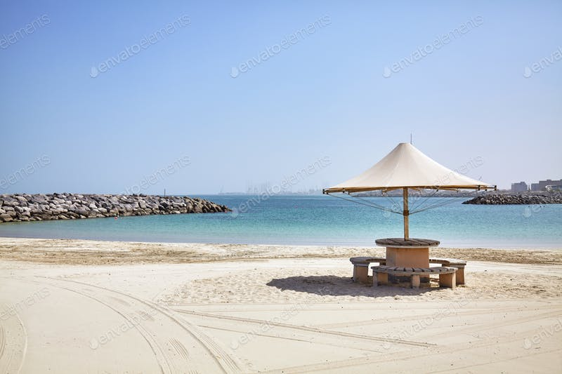 A White Umbrella In An empty Beach PSD Template.