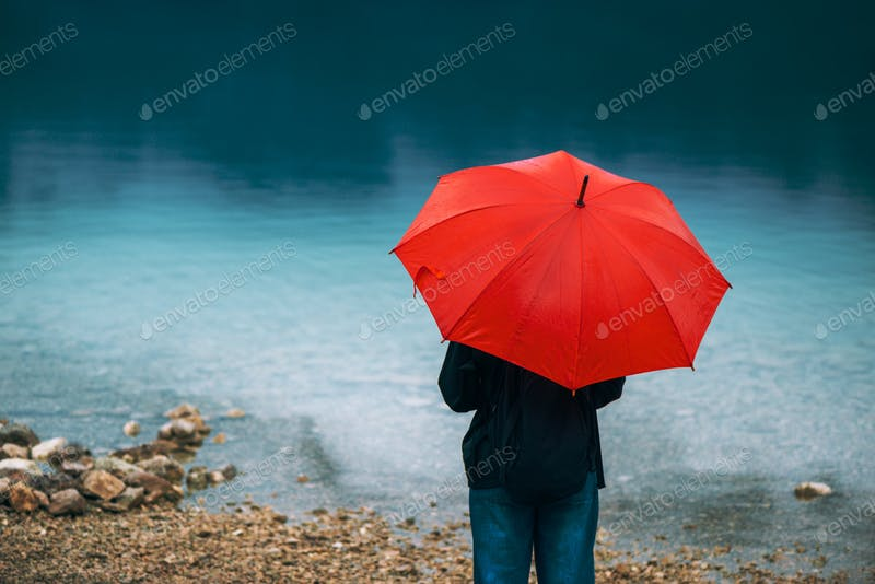 A Woman Holding A Red Umbrella Near A Lake PSD Template.