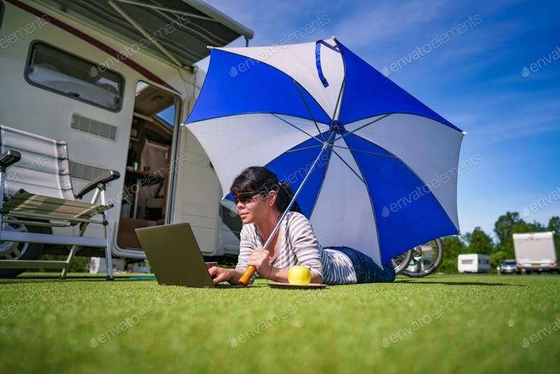A Woman Holding An Umbrella On The Grass Looking At The Laptop Mockup.