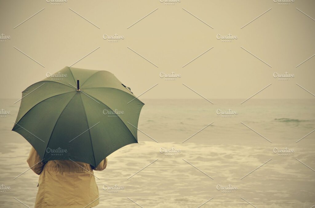 A Woman Holding Green Umbrella Near A Sea PSD Template.
