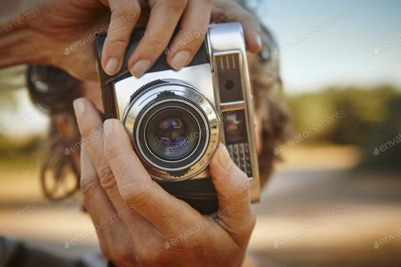 A Woman Taking Photos With A Vintage Camera PSD Mockup.
