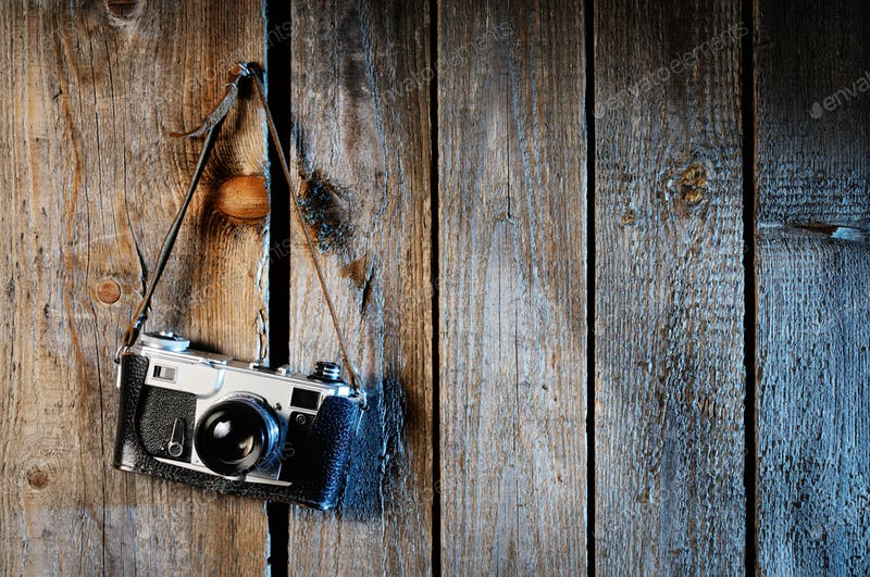 An Old Camera Hanging On The Wooden Wall PSD Mockup.