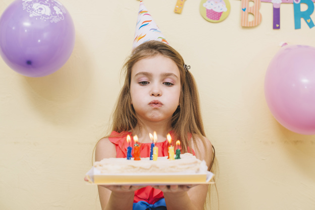 Birthday Girl holding Cake with Candles Photo