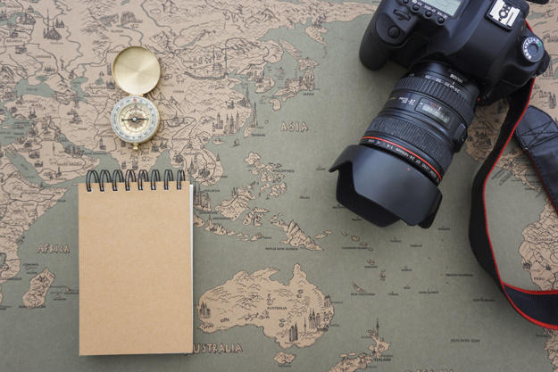 DSLR Camera, Notebook And Compass Kept On A World Map Mockup