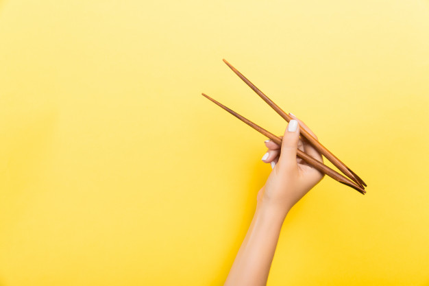 Female hand with chopsticks. traditional asian food Premium Photo