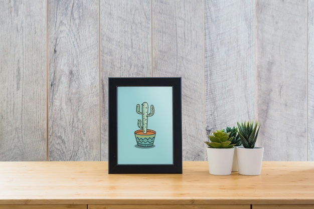 Frame mockup on table with plants Free Psd