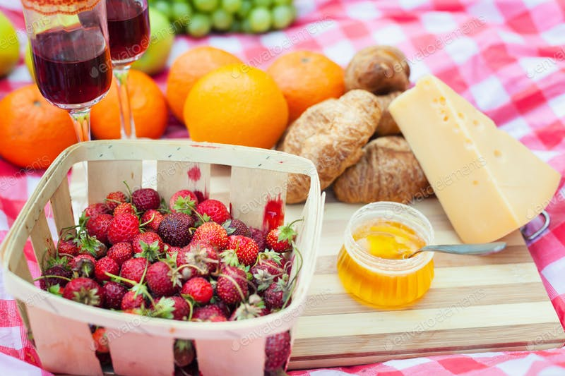Fruits And Wine Are Placed On The Blanket PSD Mockup.