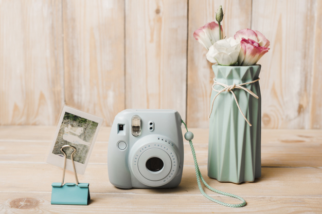 Mini Instant Camera With Flower Vase Beside