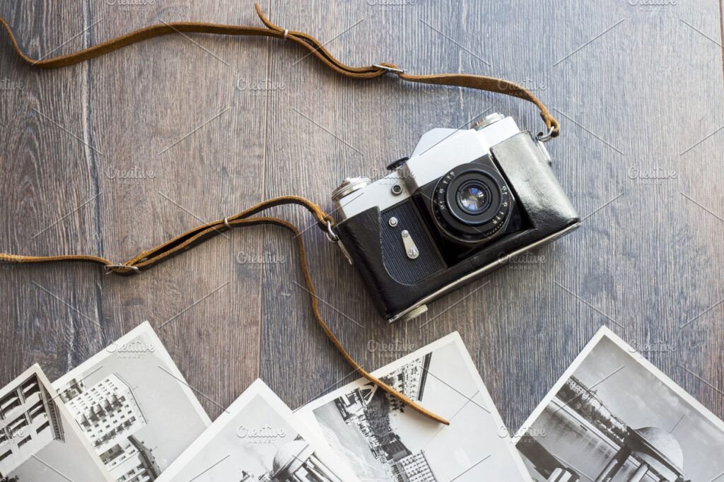 Old Photos Near A camera On The Wooden Table Mockup.
