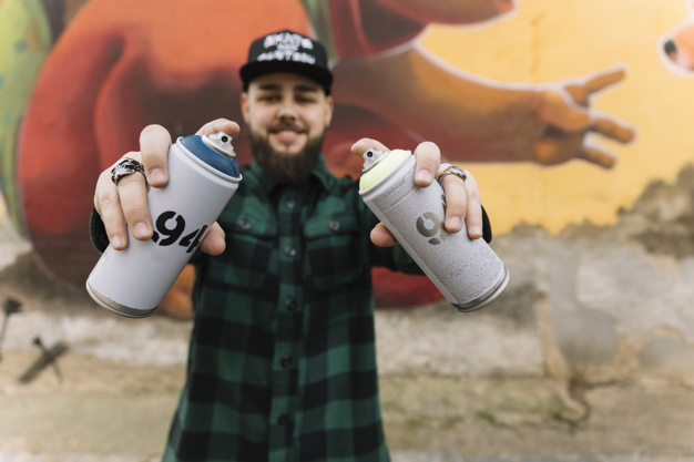 Photo of a bearded guy holding spray cans