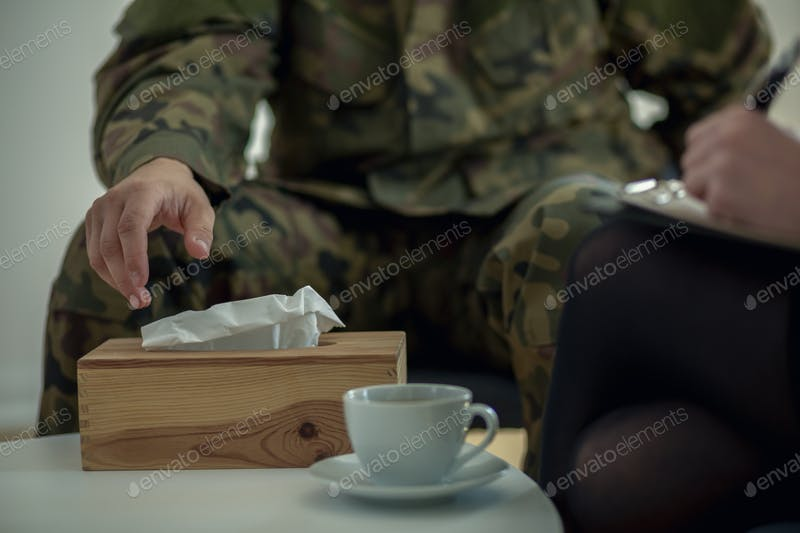 Soldier Picking Tissue Paper From Wooden Tissue Box