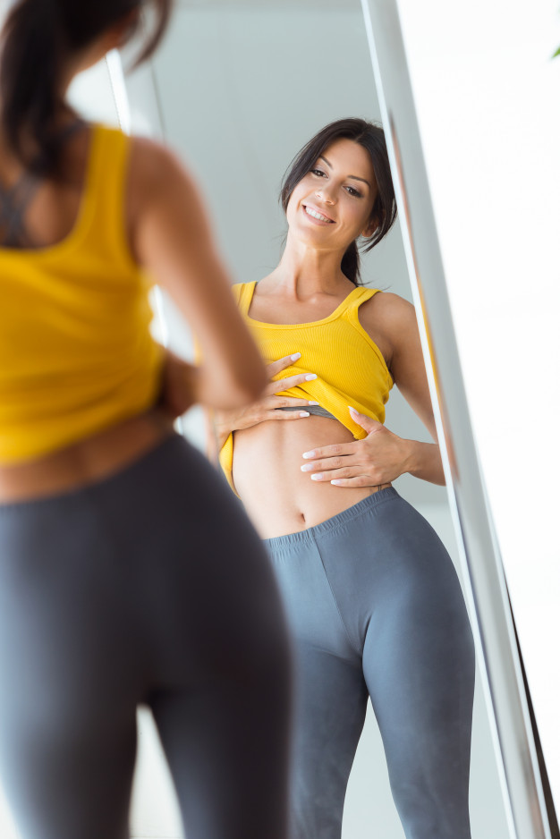 Beautiful Young Woman In Yellow Tank Top Looking At The Mirror PSD