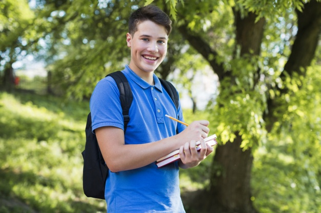 Boy Wearing Polo shirt Holding Book in Hand PSD Mockup