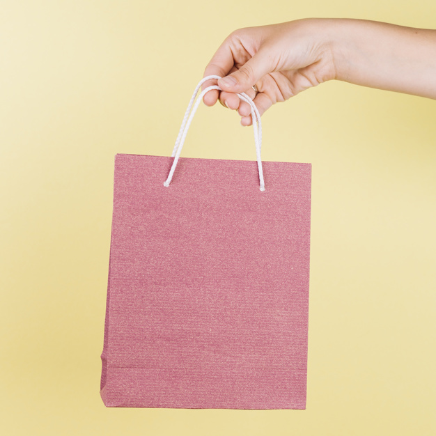 Crop Hand Holding Pink Color Gift Bag Free Photo