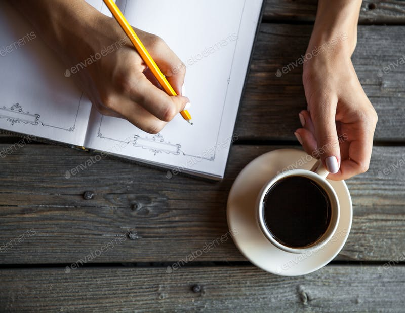 Female Hand Taking Notes With a cup of Coffee Mockup.