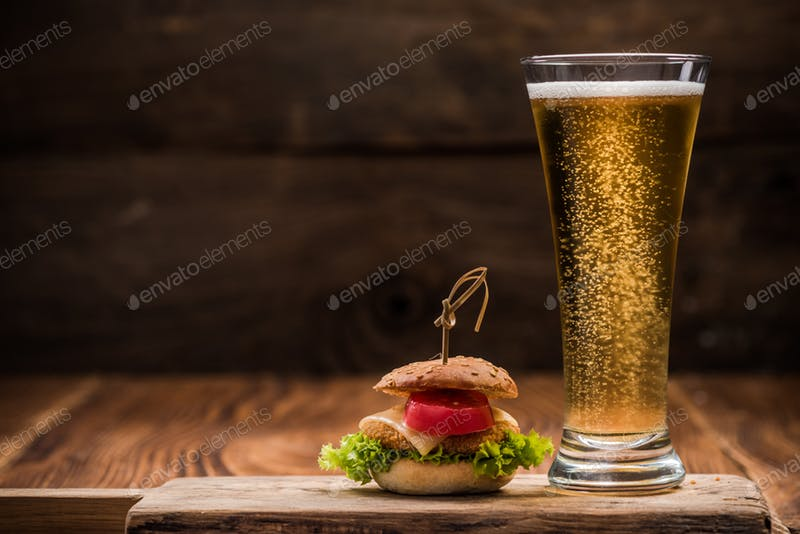 Fresh Beer Glass Placed On Wooden Board With Mini Beef Burger Beside It