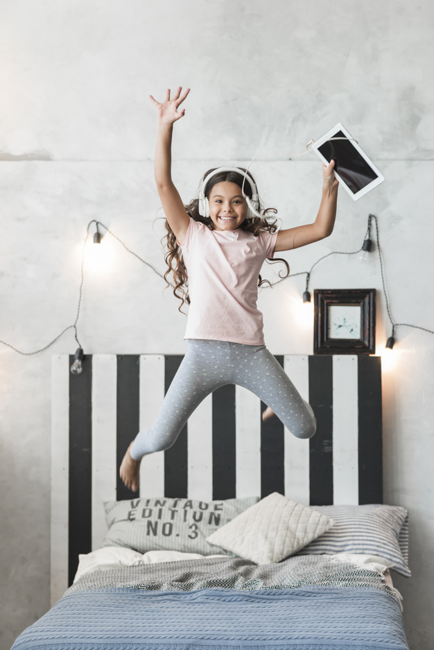 Girl Jumping in A Bed With Her Digital Headphones.