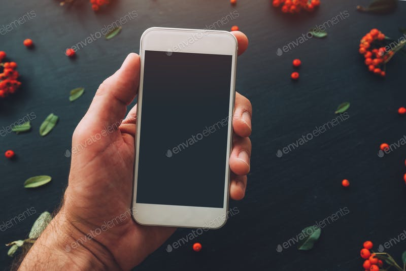 Smart phone in a man's hand PSD Mockup.