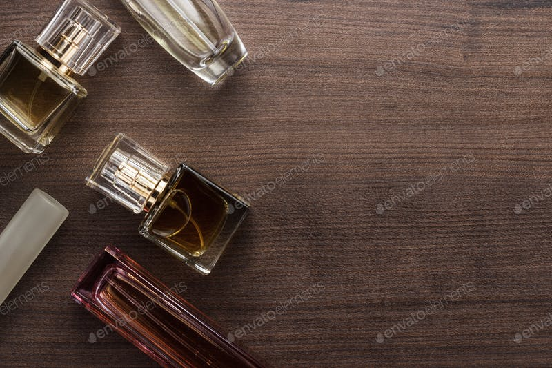 Some Perfume Bottles Placed On A Wooden Surface Mockup.