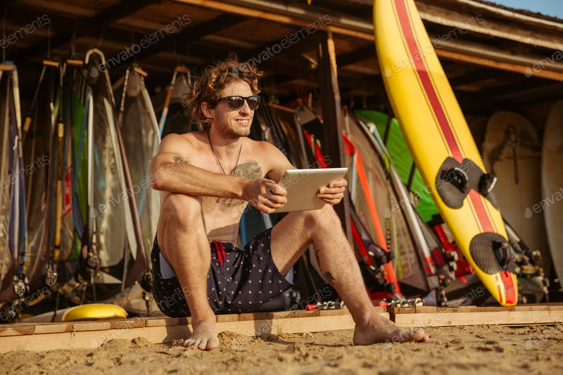 Surfer Man With A PC Tablet In His Hand Mockup.