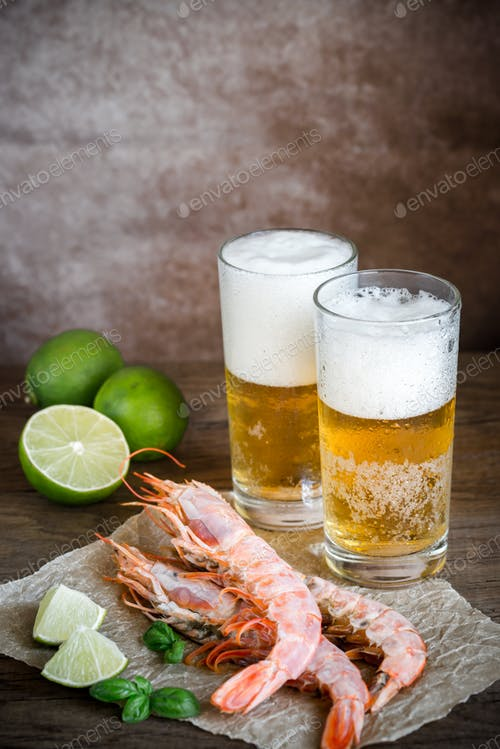 Two Lager Glass Of Beer With Shrimps And Lemon Placed On A Table PSD
