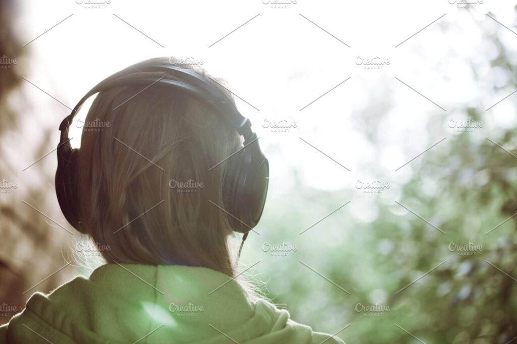 Woman Wearing Headphone facing Sun Mockup.