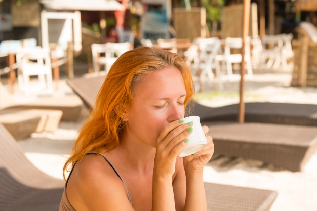 Young Woman Drinking Coffee At The Beach Template