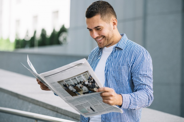 A Man reading a newspaper wearing small checkered Polo Shirt for design inspiration: