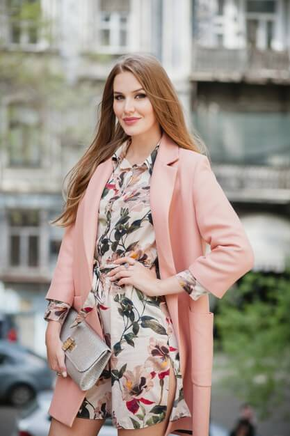 Attractive stylish smiling woman walking city street in pink coat spring fashion trend holding purse Free Photo
