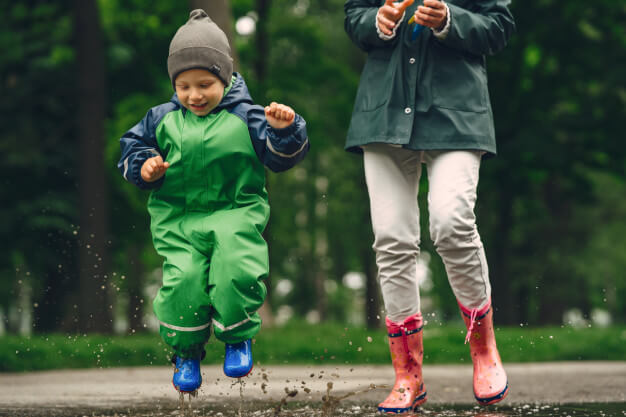 Funny kid in rain boots playing in a rain park Free Photo
