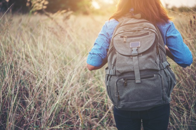 Girl making her way through the tall grass with her backpack Mockup