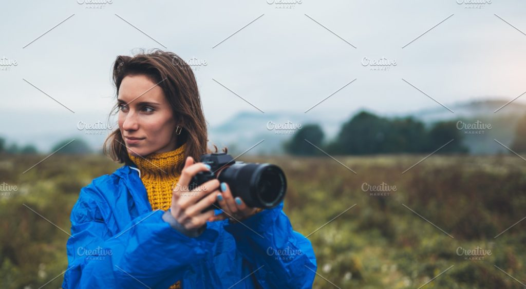 Girl photographer in a blue raincoat