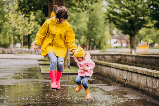 Mother with daughter having fun jumping in puddles Free Photo