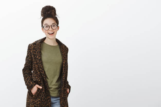 Portrait of good-looking stylish european woman with curly hair and bun haircut, wearing black trendy glasses and leopard coat, holding hands in pockets and smiling broadly Free Photo