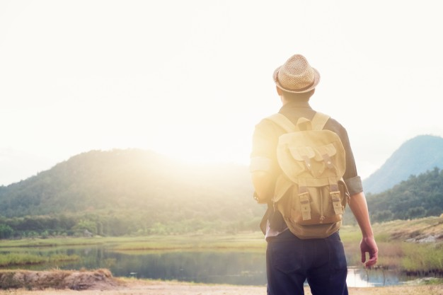 Young traveller facing the sun with his backpack PSD Design