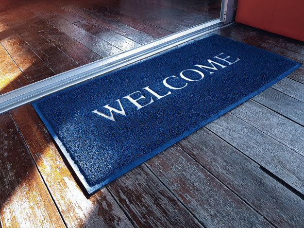 Blue doormat with welcome text in front of shop Premium Photo (1)