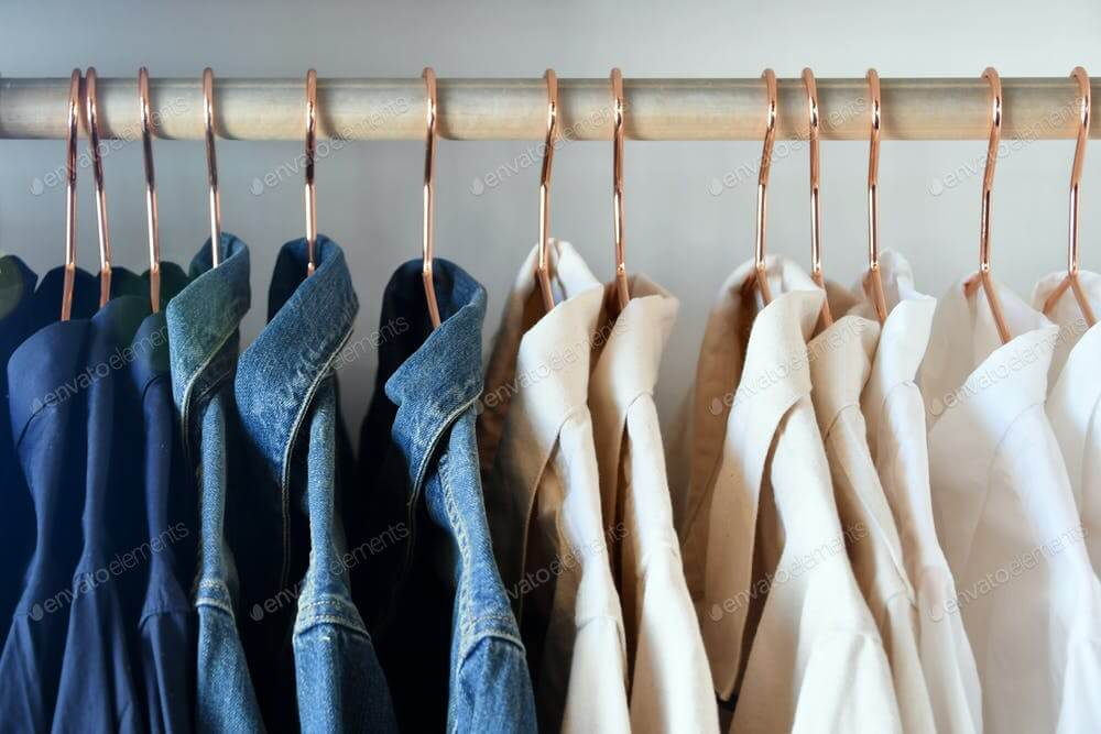 Denim, dark blue, cream & white collared shirts on brass hangers in clothing store, shop buy sell