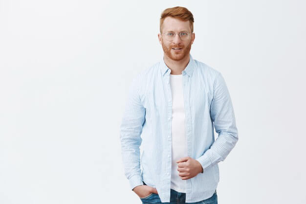 portrait-handsome-self-assured-successful-redhead-male-entrepreneur-shirt-glasses-holding-collar-smiling-with-charming-flirty-expression-grey-wall_176420-27514